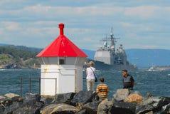 人们在Frogn,挪威观看军事运输通过海湾 库存照片