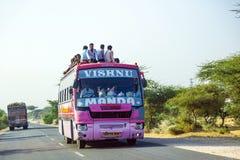 人们坐一辆陆上公共汽车的屋顶在乔德普尔城高速公路在拉贾斯坦,印度 图库摄影
