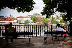 人们坐在伏尔塔瓦河河岸的长凳并且看Hradcany在布拉格,捷克。 免版税库存照片