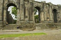 人们坐在入口对圣地亚哥Apostol大教堂的废墟在卡塔戈,哥斯达黎加 免版税图库摄影