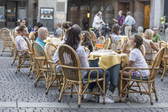 人们坐在街道咖啡馆的小的桌上 免版税图库摄影
