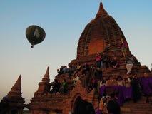 人们坐寺庙观看日出 免版税库存照片