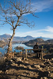 人们坐长凳有美妙的风景看法在朱利安阿尔卑斯 免版税库存照片