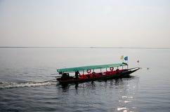 人们坐,并且推进长尾巴小船去到Donsawan海岛 库存照片