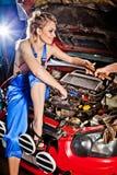 人给女孩一个工具修理汽车 免版税库存照片