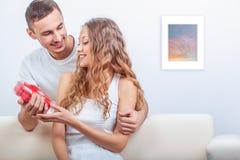 年轻人给她一件心形的礼物 库存图片