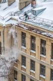 人从屋顶的清洁雪 库存图片