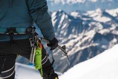 A年轻人登山人的关闭在他的手上拿着站立在山顶的一个冰轴高在山 极其体育运动 库存照片