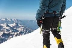 A年轻人登山人的关闭在他的手上拿着站立在山顶的一个冰轴高在山 极其体育运动 图库摄影
