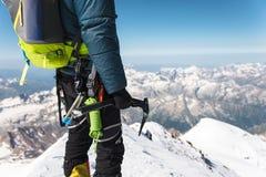 A年轻人登山人的关闭在他的手上拿着站立在山顶的一个冰轴高在山 极其体育运动 免版税图库摄影