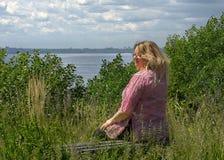 年轻人40岁肥胖妇女坐在清洁的一条长凳在伏尔加河俄罗斯上 库存照片