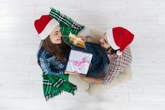 人给当前礼物盒妇女圣诞节假日愉快的夫妇穿戴新年圣诞老人帽子盖帽,坐地板 免版税库存图片