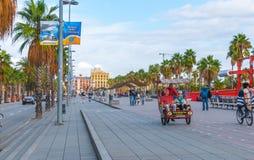 人们户外,在人力车,在自行车&走,利用在一个广场的温暖的天气在隧道交通上 免版税图库摄影