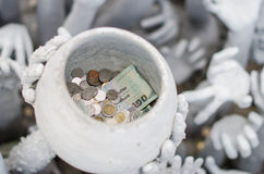 人们投了在雕象碗的金钱 下面从地狱举的手 在Wat荣Khun 免版税库存图片