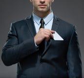 人去掉从口袋的白色卡片 免版税图库摄影