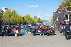 人们放松在阳光下,著名Cafe在左边的de Sluyswacht, Montelbaans塔是可看见的在背景中 免版税图库摄影