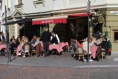 人们是松弛在一个晴朗的咖啡馆大阳台在老镇维尔纽斯,立陶宛 免版税库存图片