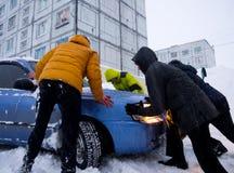 人们是汽车在雪黏附的推出随风飘飞的雪 免版税库存照片