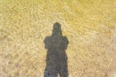 人类本性水的阴影在沙子背景的 免版税库存照片