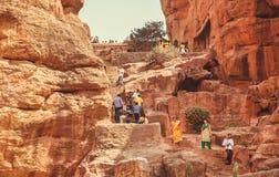 人们步行沿着向下通过古老洞的台阶与6世纪印度寺庙 免版税库存照片