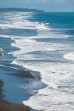 人们沐浴在他染黑火山的熔岩海滩在太平洋在Jaco,哥斯达黎加 免版税图库摄影