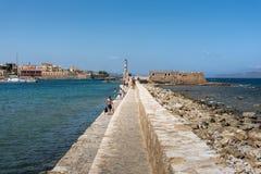 人们沿港口墙壁走在克利特海岛上的干尼亚州镇 免版税图库摄影