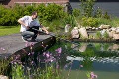 人洗涤他的庭院池塘 免版税库存图片