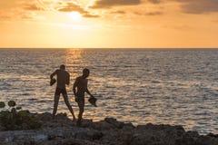 年轻人去游泳在日落 库存图片