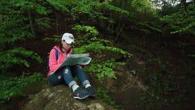 年轻人麻烦了有背包的旅游妇女看对她的地图和举眼睛检查与地方地形的 股票视频