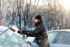 人从玻璃清洗雪在汽车 免版税库存照片