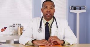 黑人医生谈话与照相机 免版税图库摄影