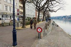 人们由河沿走在莱茵河银行在巴塞尔,瑞士 免版税库存照片