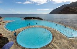 人们由游泳池休息在波尔图Medeira的da Cruz 免版税库存图片