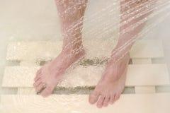 人洗他的在阵雨的脚 库存图片