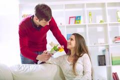 年轻人给他的女朋友带来花 免版税库存图片