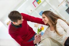 年轻人给他的女朋友带来花 库存图片