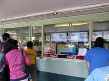 人们站在队中在彩虹免下车服务 免版税库存照片