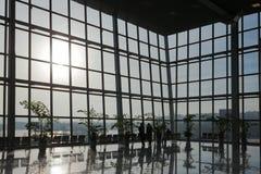 人们站立在玻璃墙在商业中心 库存照片