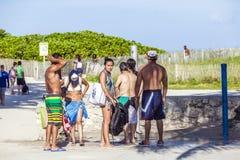 人们等在海洋驱动海滩阵雨 免版税库存照片