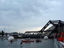 人们等待沿栏杆和在小船和喷气机滑雪的在wate 库存图片