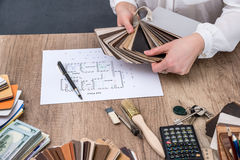 人建筑师画与色板显示的一个房子计划家具的, 免版税库存图片