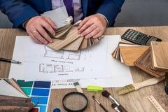 人建筑师画与色板显示的一个房子计划家具的, 免版税库存照片