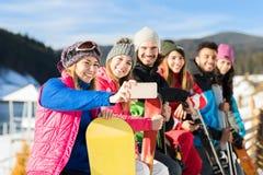 人们编组与雪板和滑雪胜地雪冬天山快乐的采取的Selfie照片 免版税图库摄影