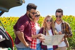 人们编组看室外路线图常设向日葵的领域 图库摄影