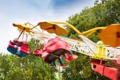 人们获得乐趣在游乐园转盘 免版税库存照片