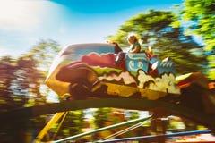 人们获得在过山车的乐趣在公园 免版税库存图片
