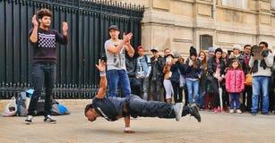 人们观看一无家可归的streetdancer做breakdance并且跳舞在巴黎街道的移动挣一些钱 免版税库存图片