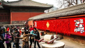 人们试验五谷磨房和石头路辗乐趣的在寺庙市场在东岳庙在汉语新春佳节期间在北京,池氏 股票视频