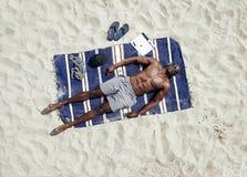 年轻人说谎赤裸上身在晒日光浴的席子 图库摄影