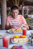 年轻人画象吃早餐在异乎寻常 库存图片
